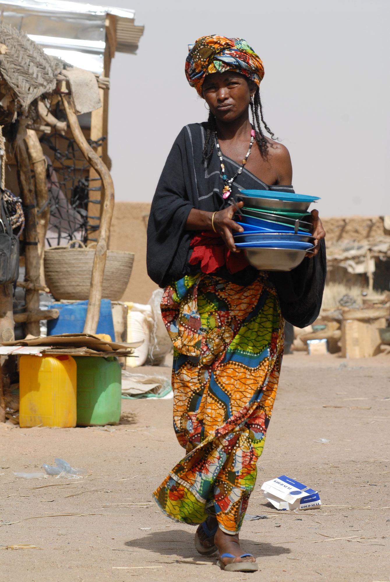 Een vrouw, waarschijnlijk Touareg loopt met een stapel borden.