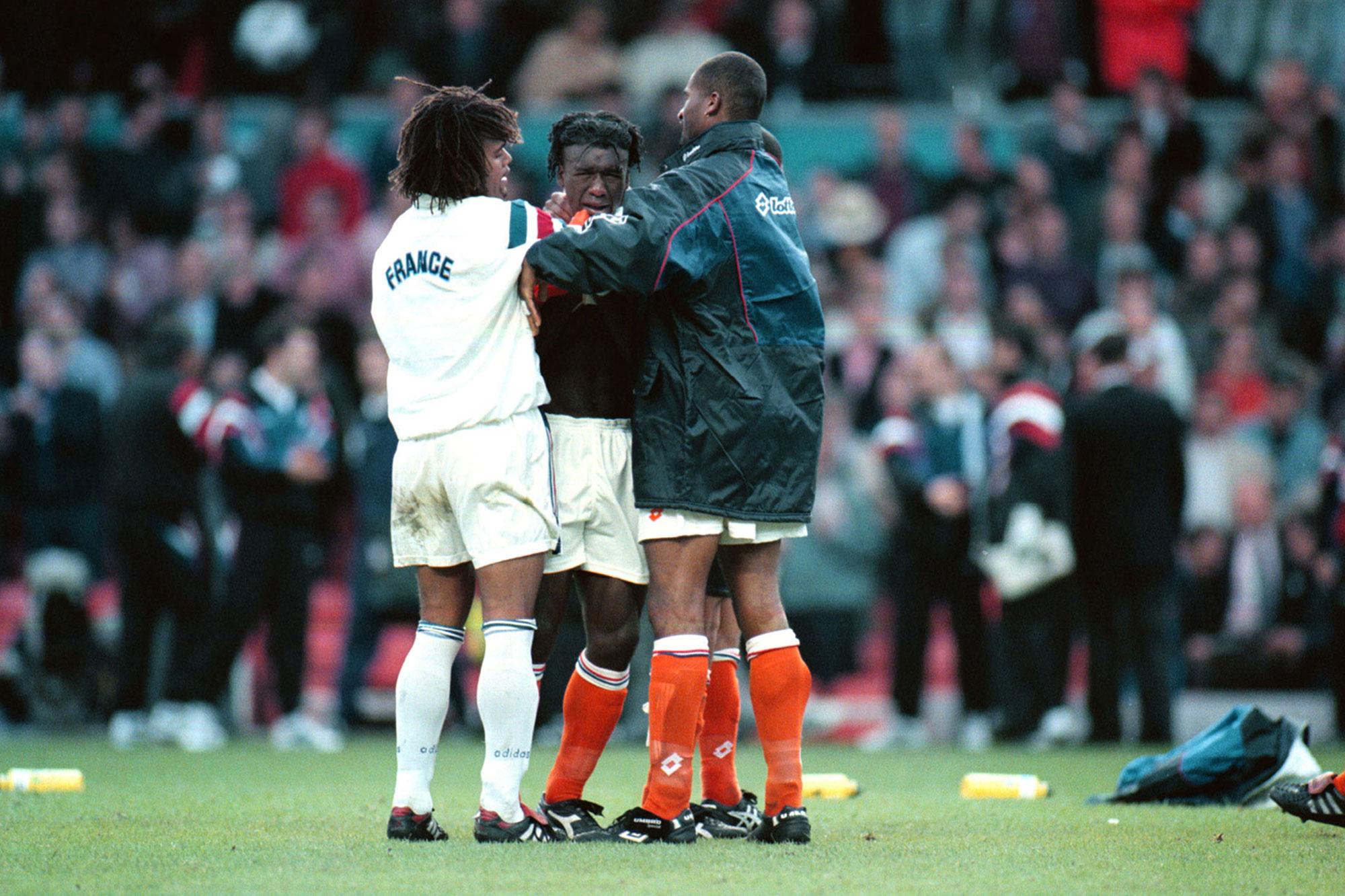 Scheidsrechter haalt twee voetballers uit elkaar