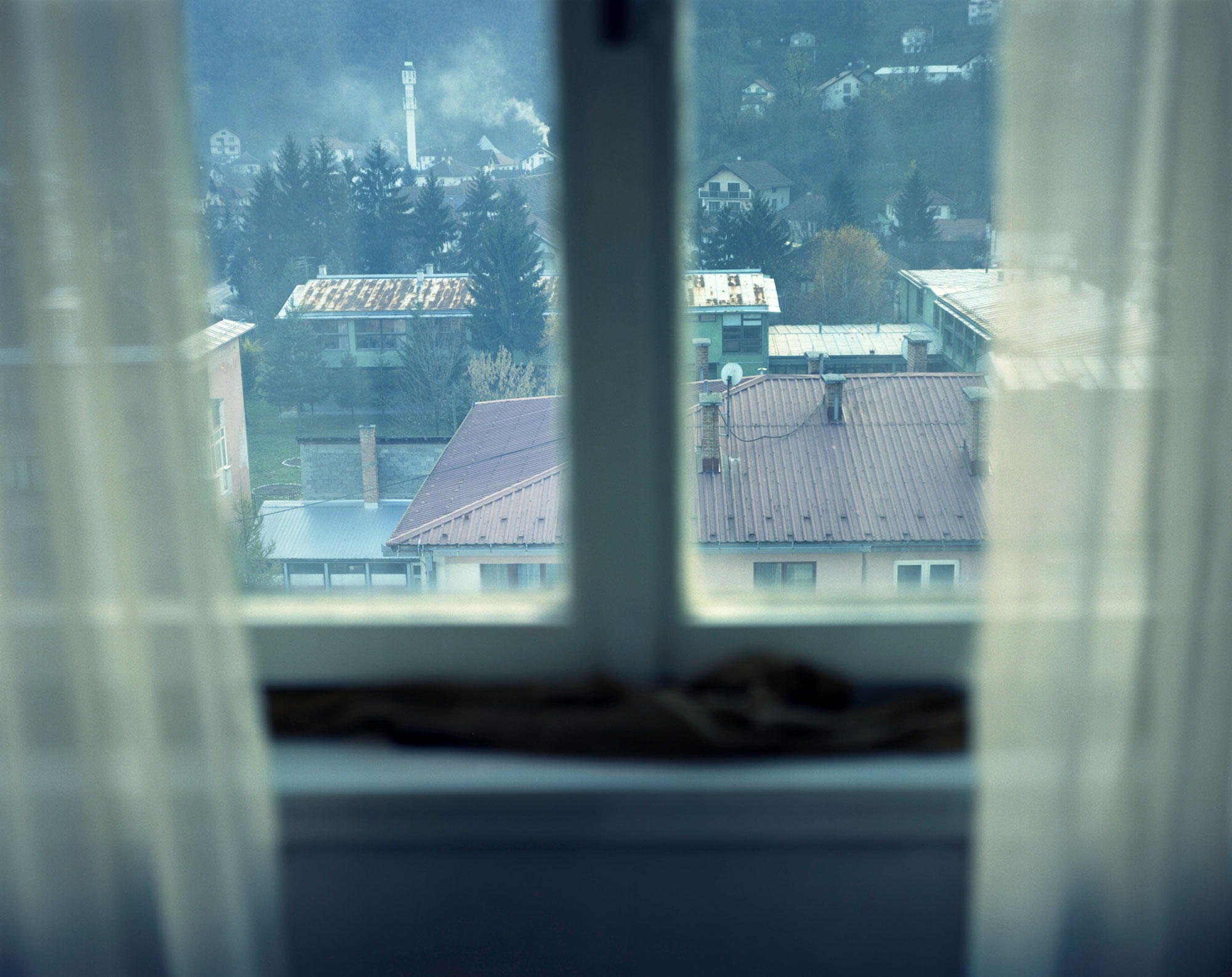 Foto van raam met vitrage en uitzicht in Bosnie