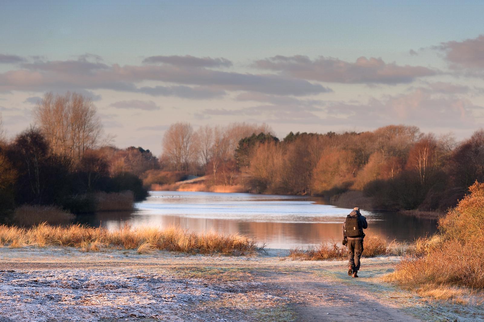 Een weids landschap met een wandelaar