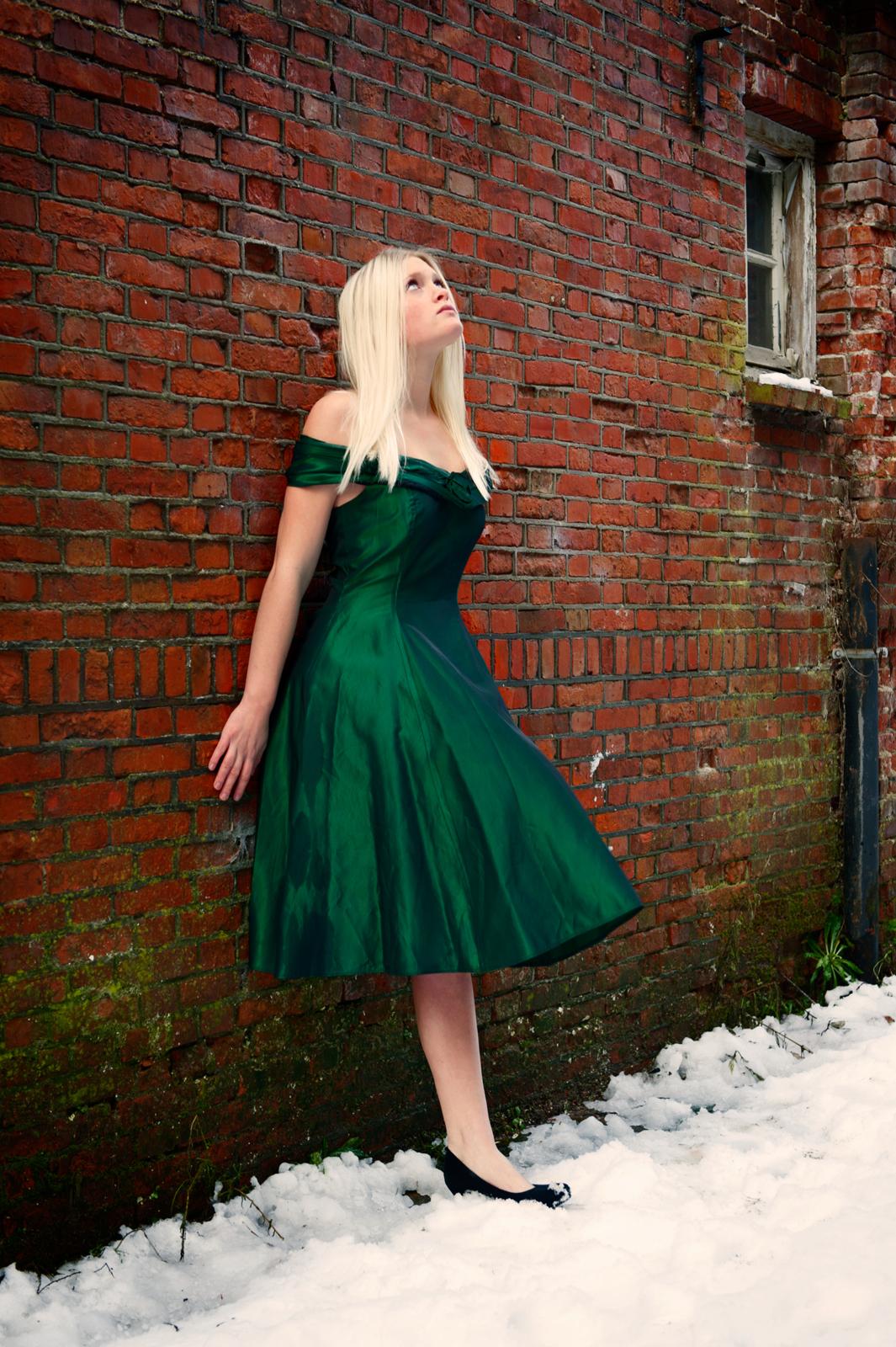 Vrouw leunt tegen muur met groene jurk aan