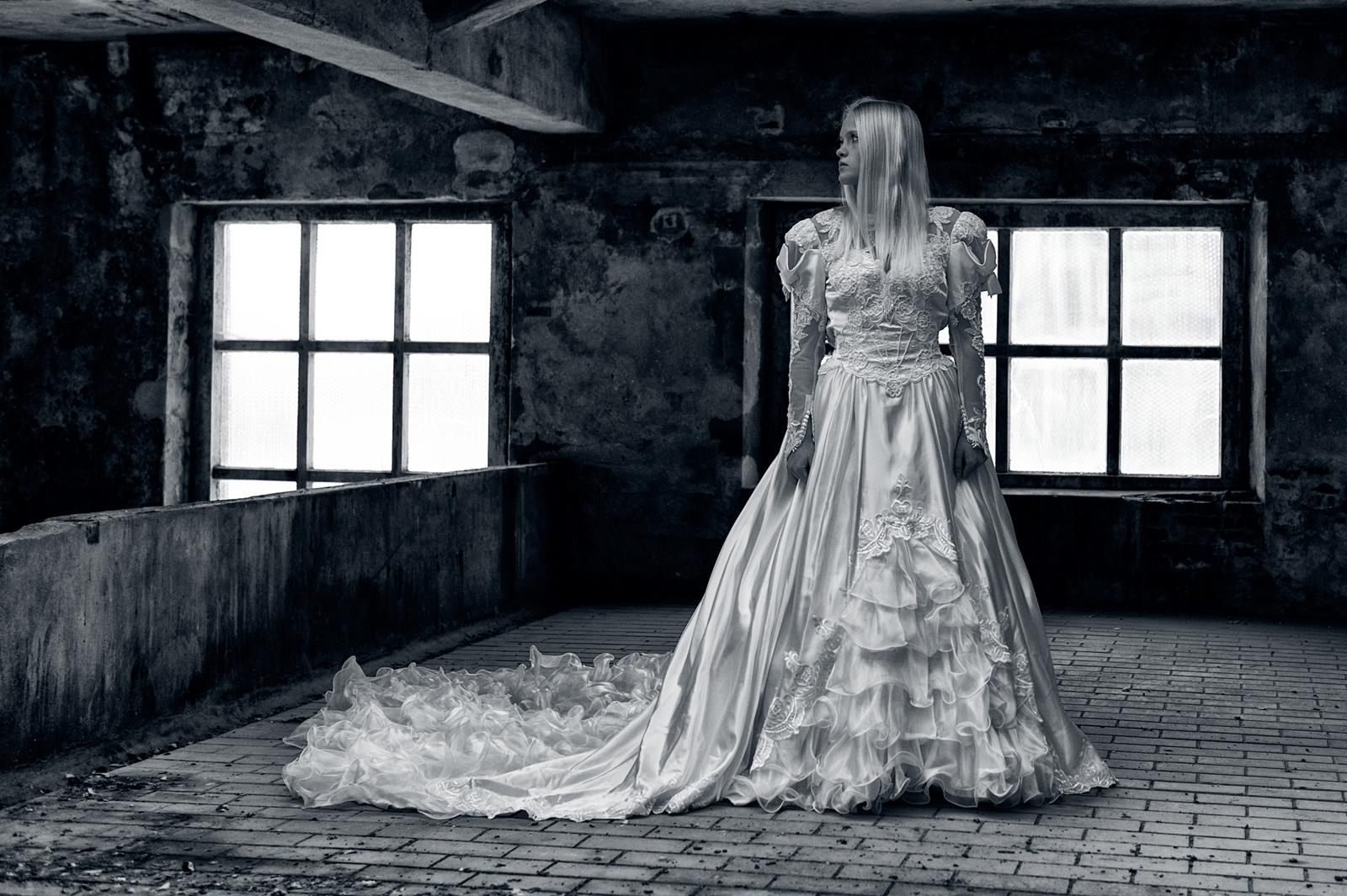 Vrouw in oude fabriek met lange trouwjurk
