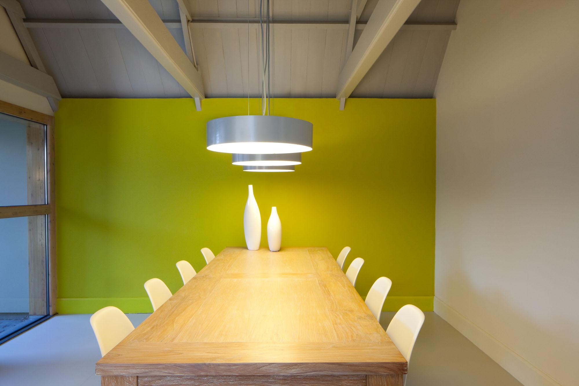 Foto van een vergadertafel met groene achterwand