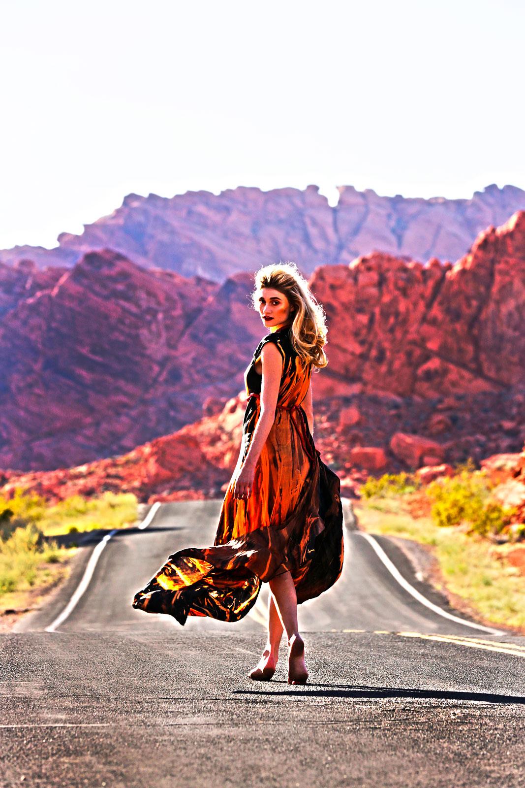 Foto van vrouw die omkijkt op autoweg met wapperende rode jurk