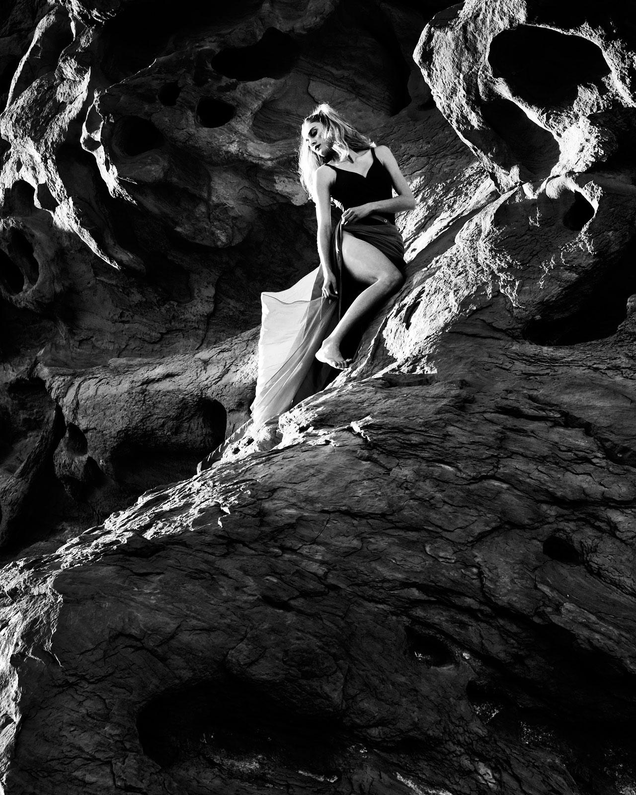 Foto in zwartwit van vrouw die steunt tegen rots in lange jurk
