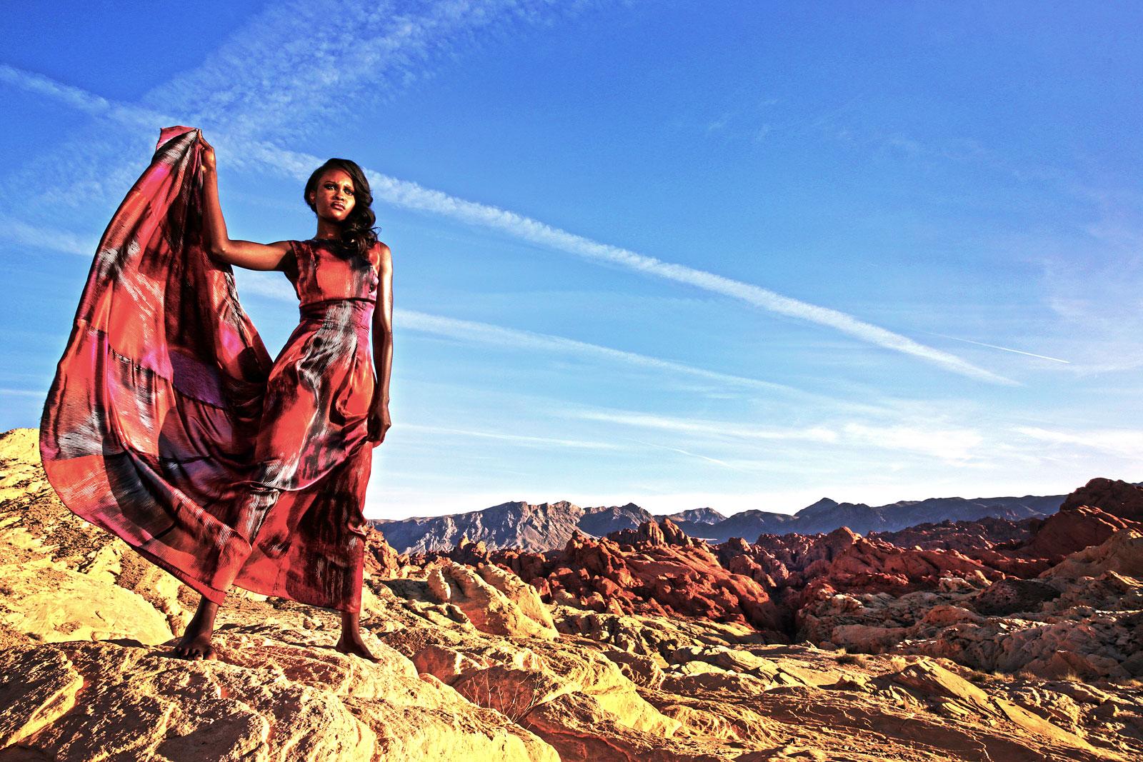 Foto van vrouw in rode jurk in ruig landschap