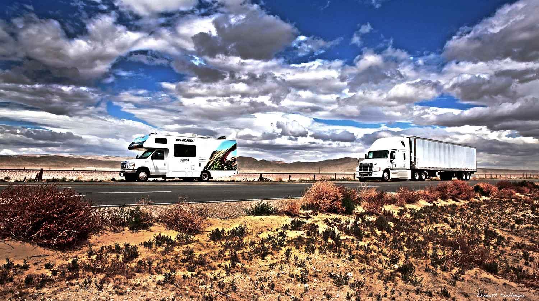 Foto van camper op de highway met vrachtwagen