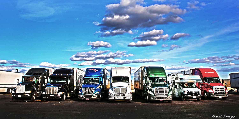Foto van camper tussen Amerikaanse vrachtauto's langs weg