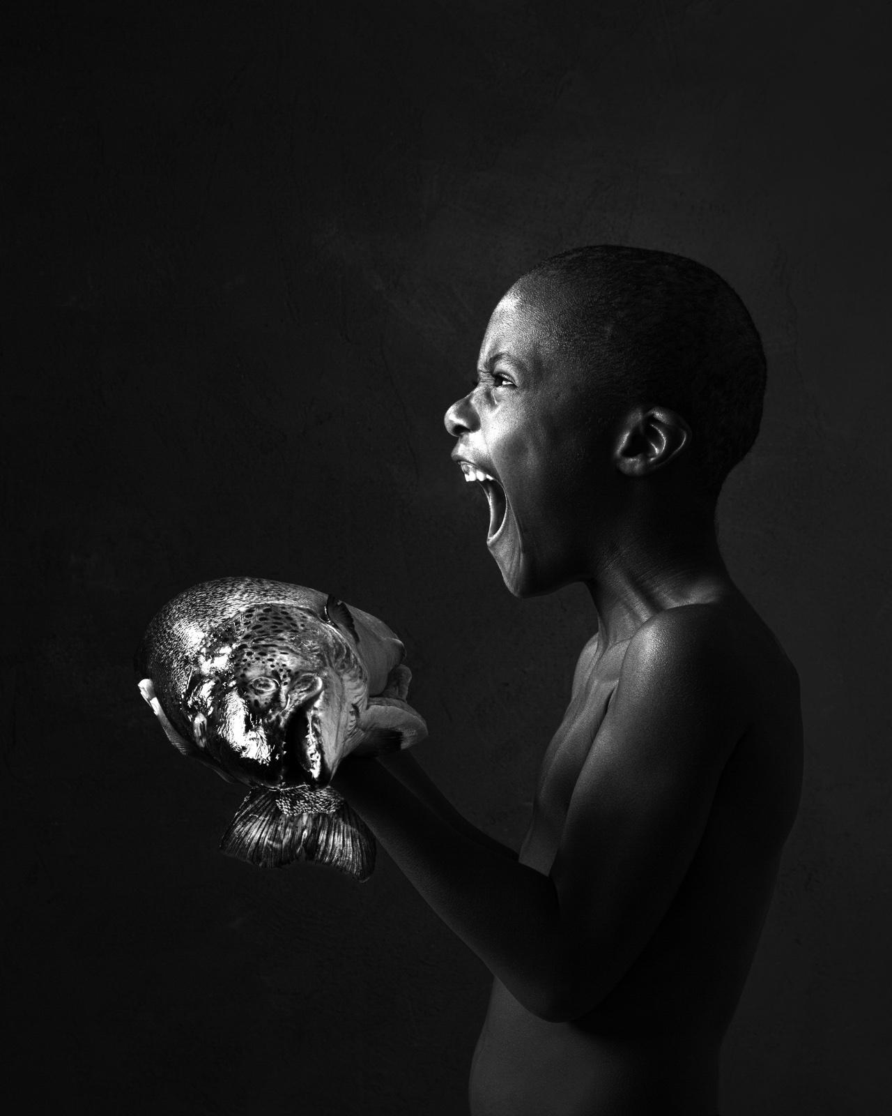 Kind met vis in handen schreeuwend