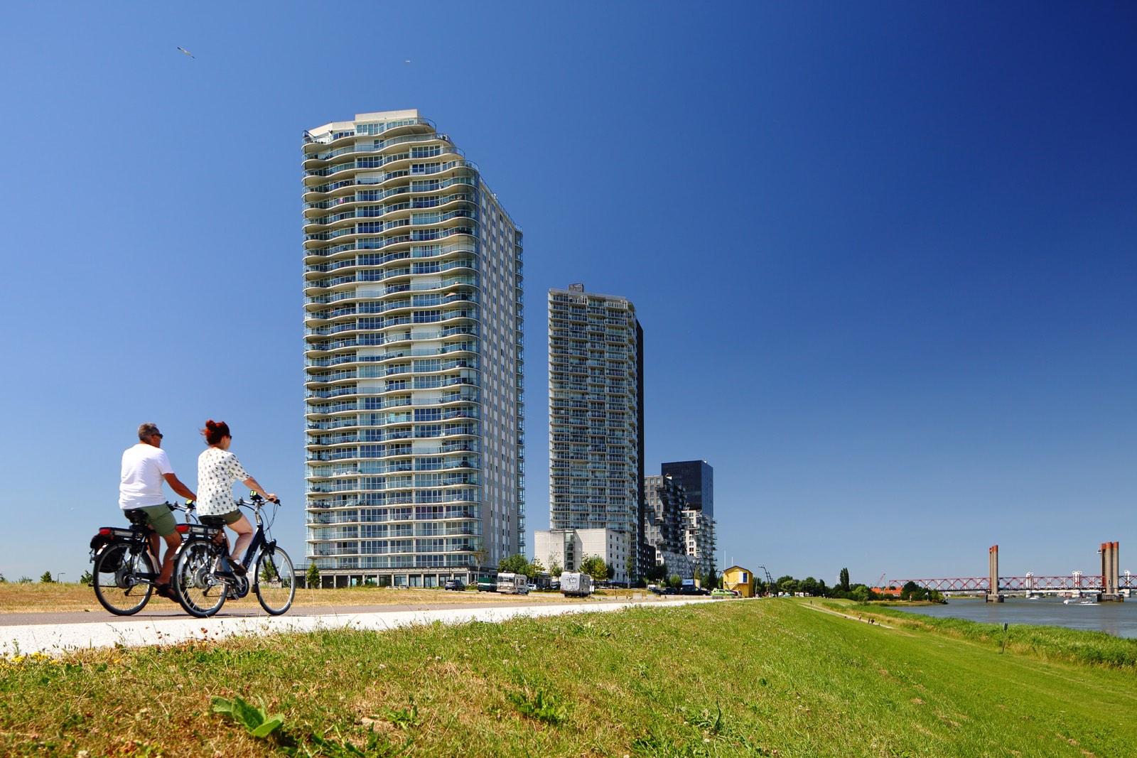 Man en vrouw op fiets op dijk met futuristische flats door Wilmar Dik