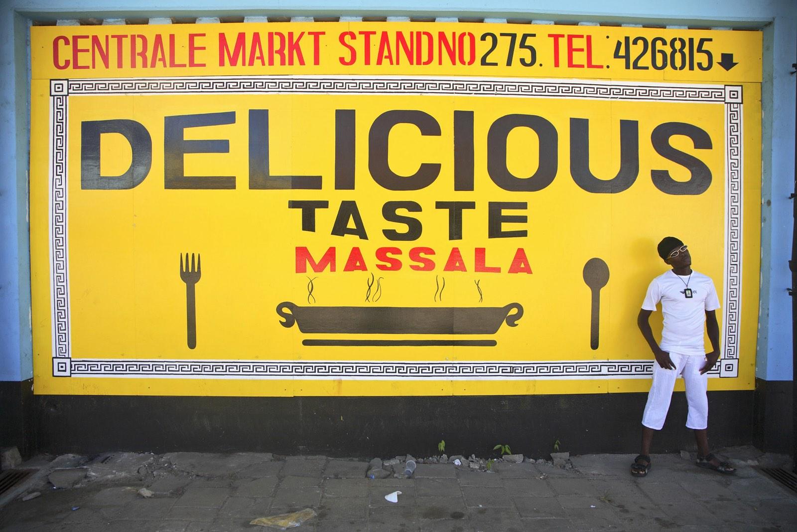 Zwarte man in Paramaribo op straat bij groot reclamebord