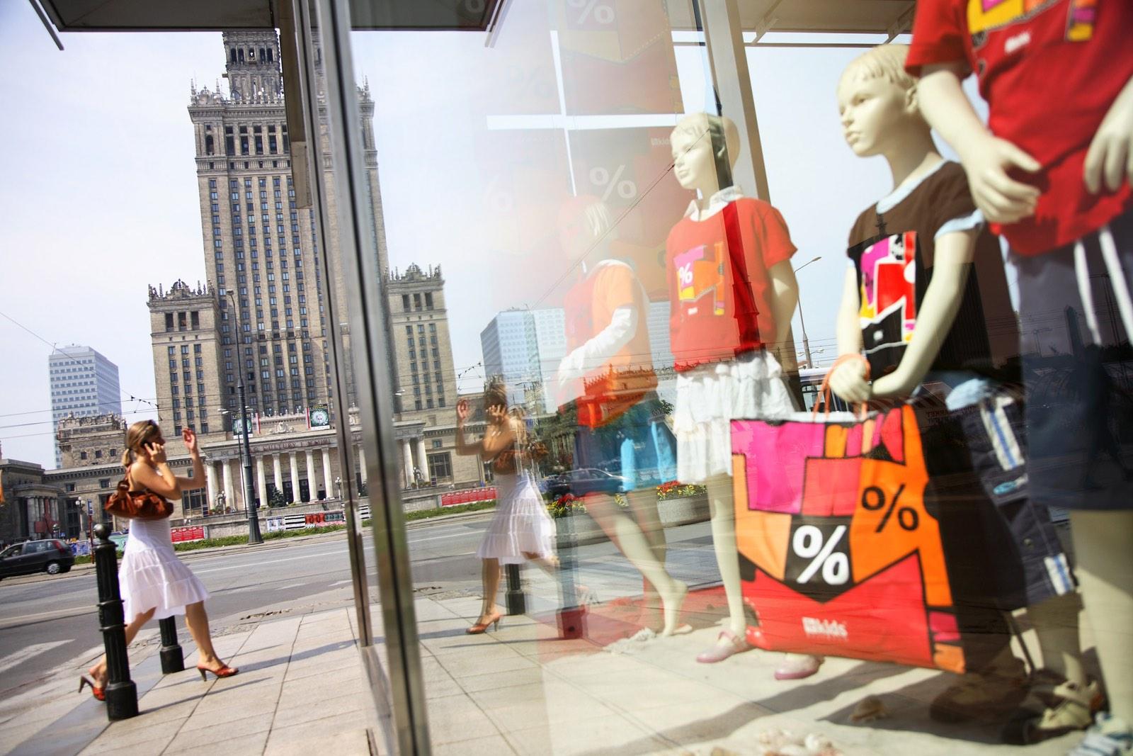 Vrouw steekt over in stad naast etalage winkel