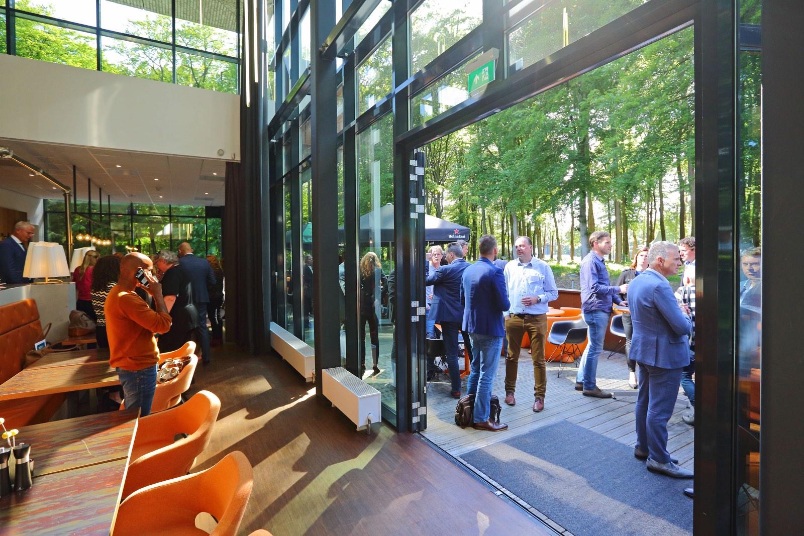 Interieur gebouw met uitkijk naar buiten en bezoekers