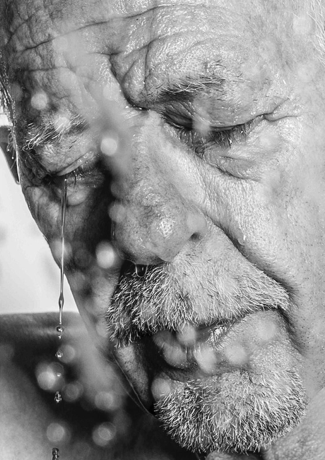 Foto van Mona Alikah van man met gesloten ogen en traan van gezicht druipend