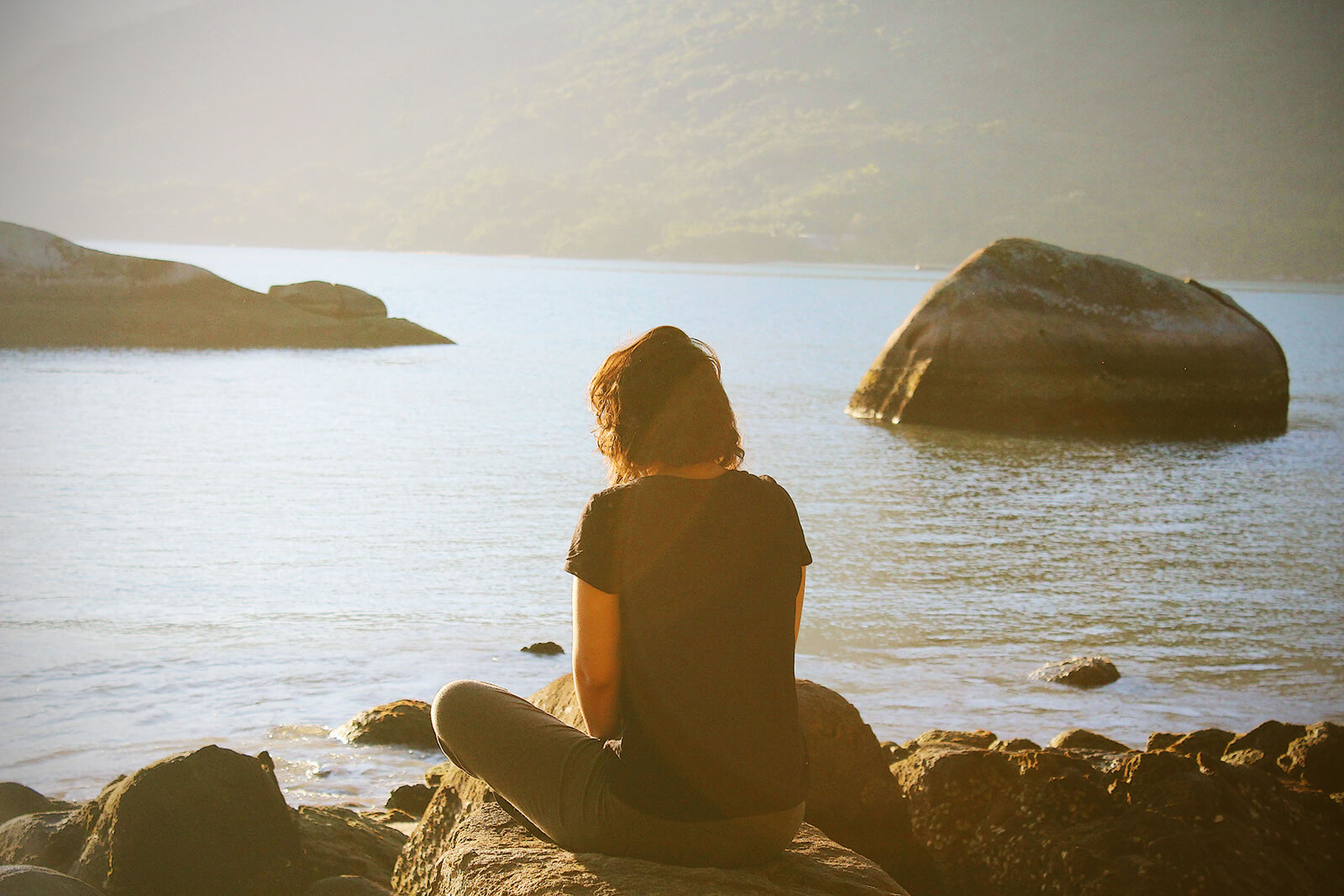 Woman meditating on a lake shore