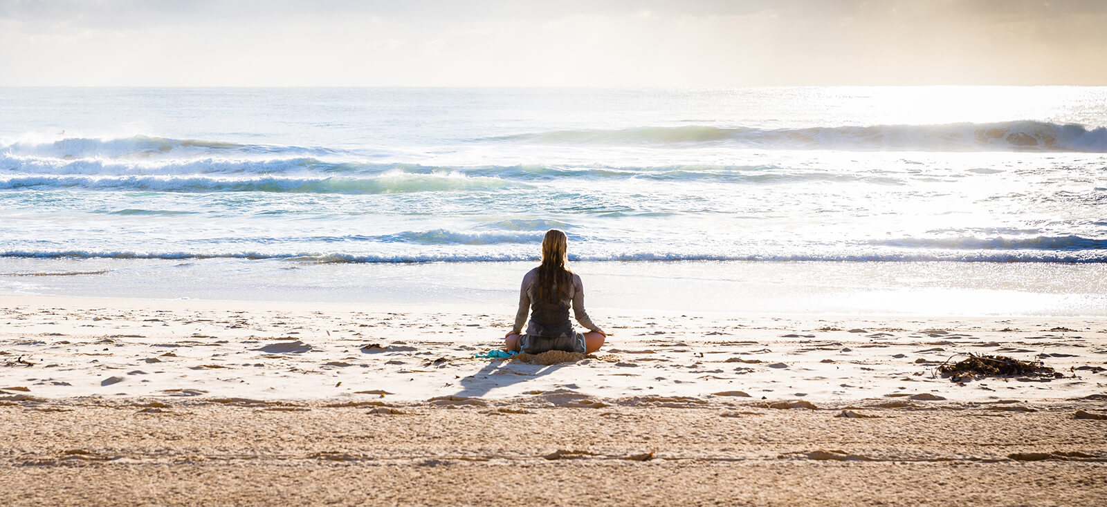 Woman meditating on a beach shore