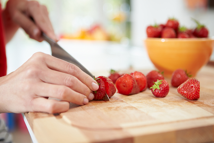 cutting strawberries on wood cutting board