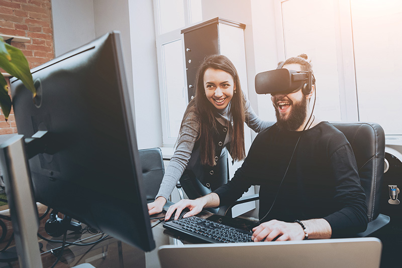 A VR developer with headset on next to a computer