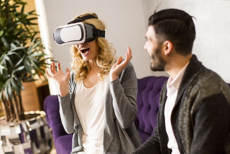 A woman excited to be in a VR headset with a man sitting next to her