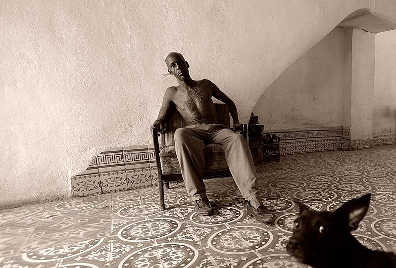 foto van man op stoel buiten met ontbloot bovenlijf in Cuba