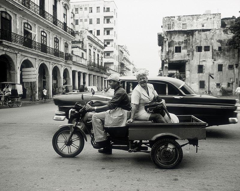 zwartwitfoto van een brommer met bak eraan vast op straat in Cuba met een toerist die vervoerd wordt