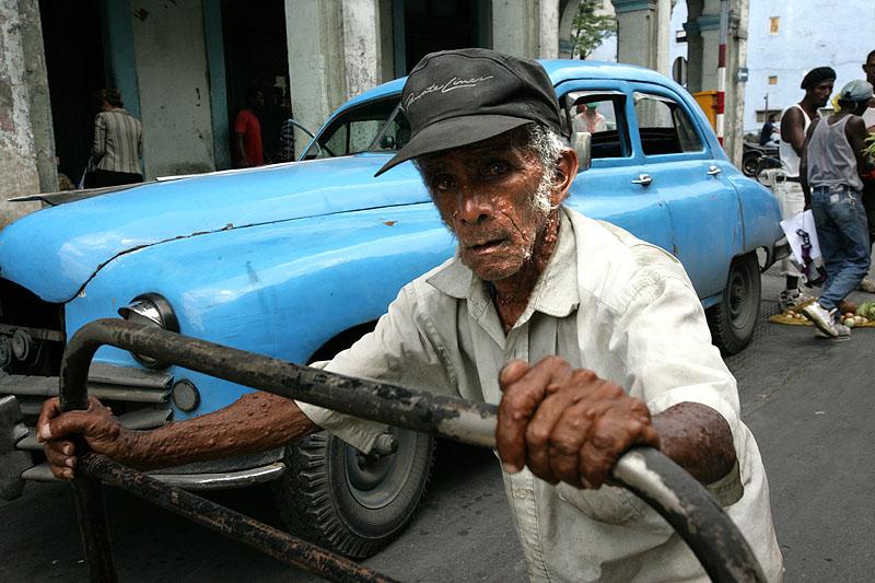 foto van man die kar vasthoudt in een drukke straat met blauwe auto op achtergrond n Cuba
