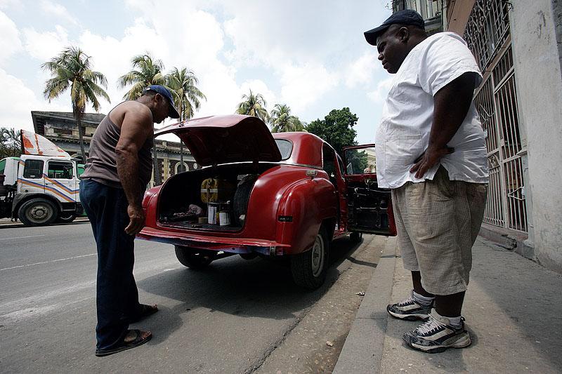foto van twee mannen op straat in Cuba bij rode auto die de achterklep open heeft