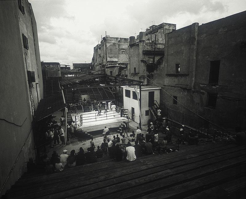 zwartwit foto van boksring met publiek midden tussen de huizen in Cuba
