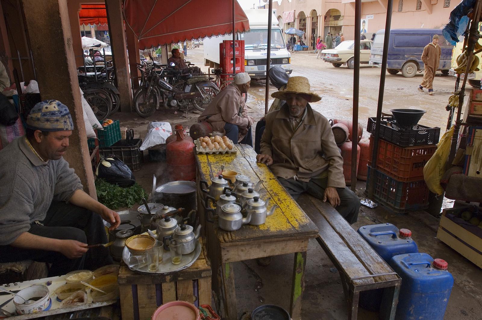 foto van twee mannen die aan een tafel op straat zitten, de ene maakt thee, in Marokko