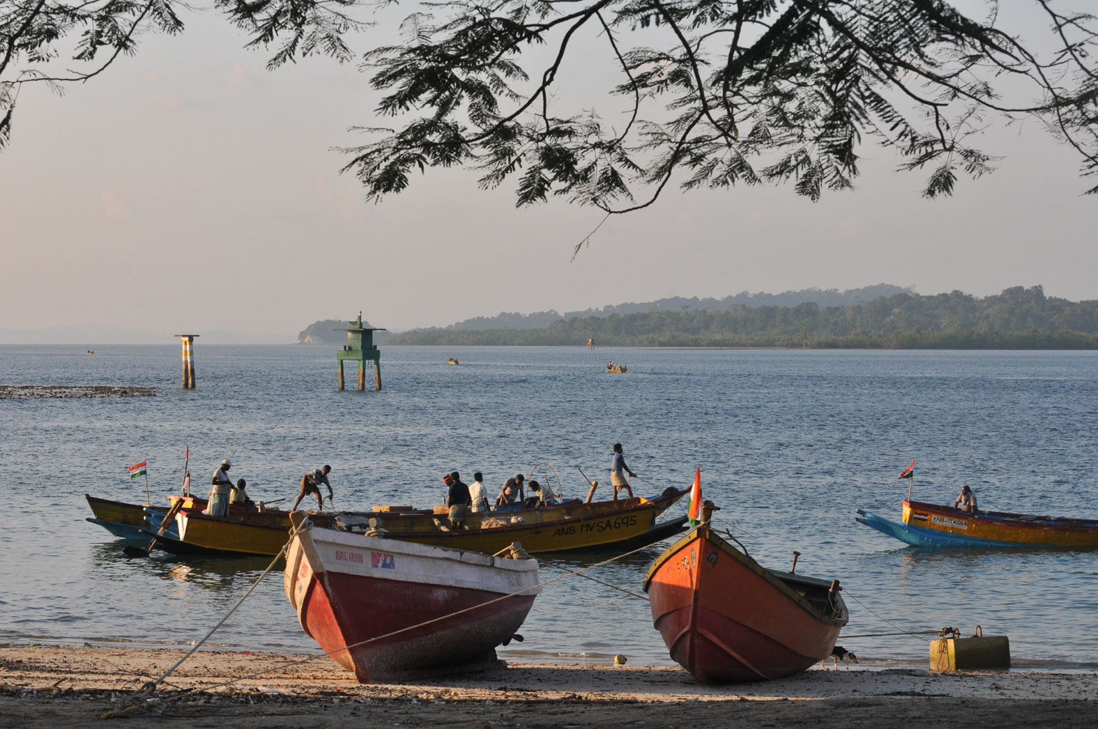 foto van vissersboten aan de kant en in het water met vergezicht naar land aan overkant