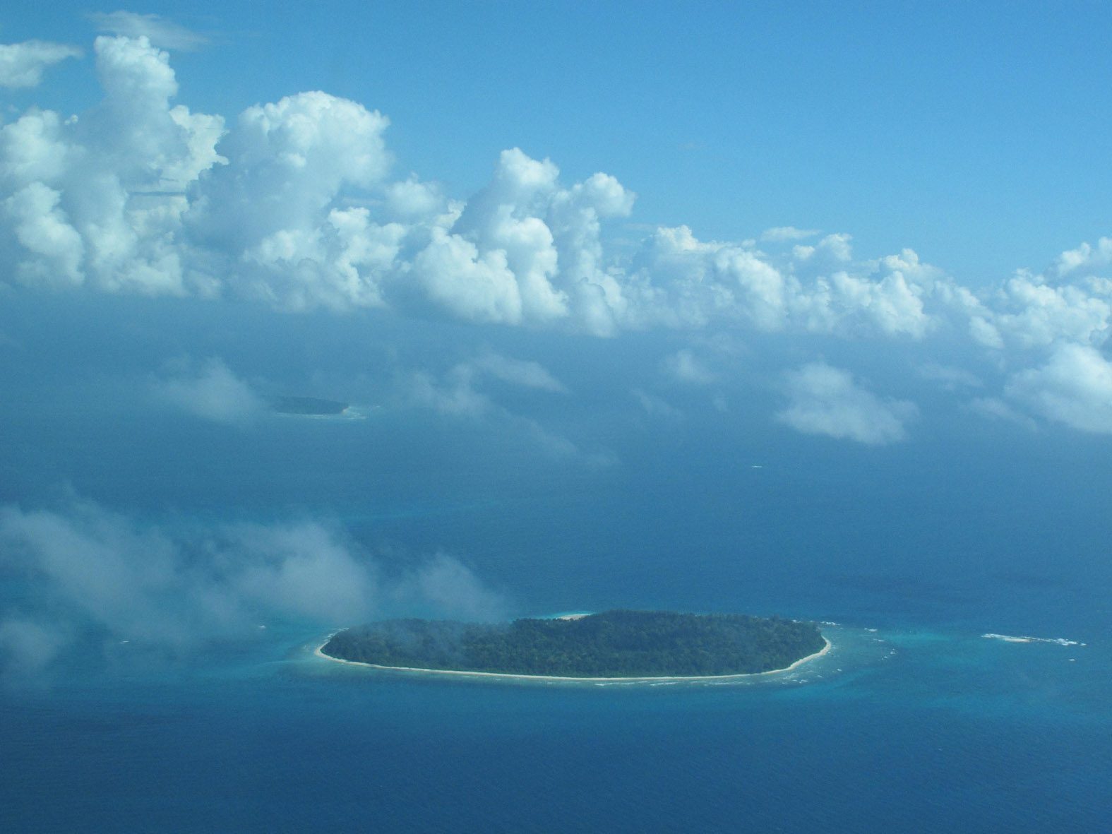 foto van een eiland in de zee van bovenaf met wolkenluchten