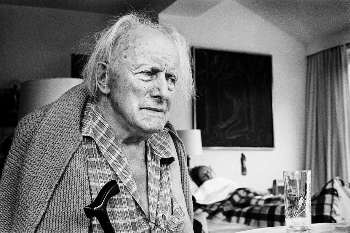 foto van Paul Delvaux, de bijna blinde kunstenaar met in de achtergrond zijn zieke geliefde in bed