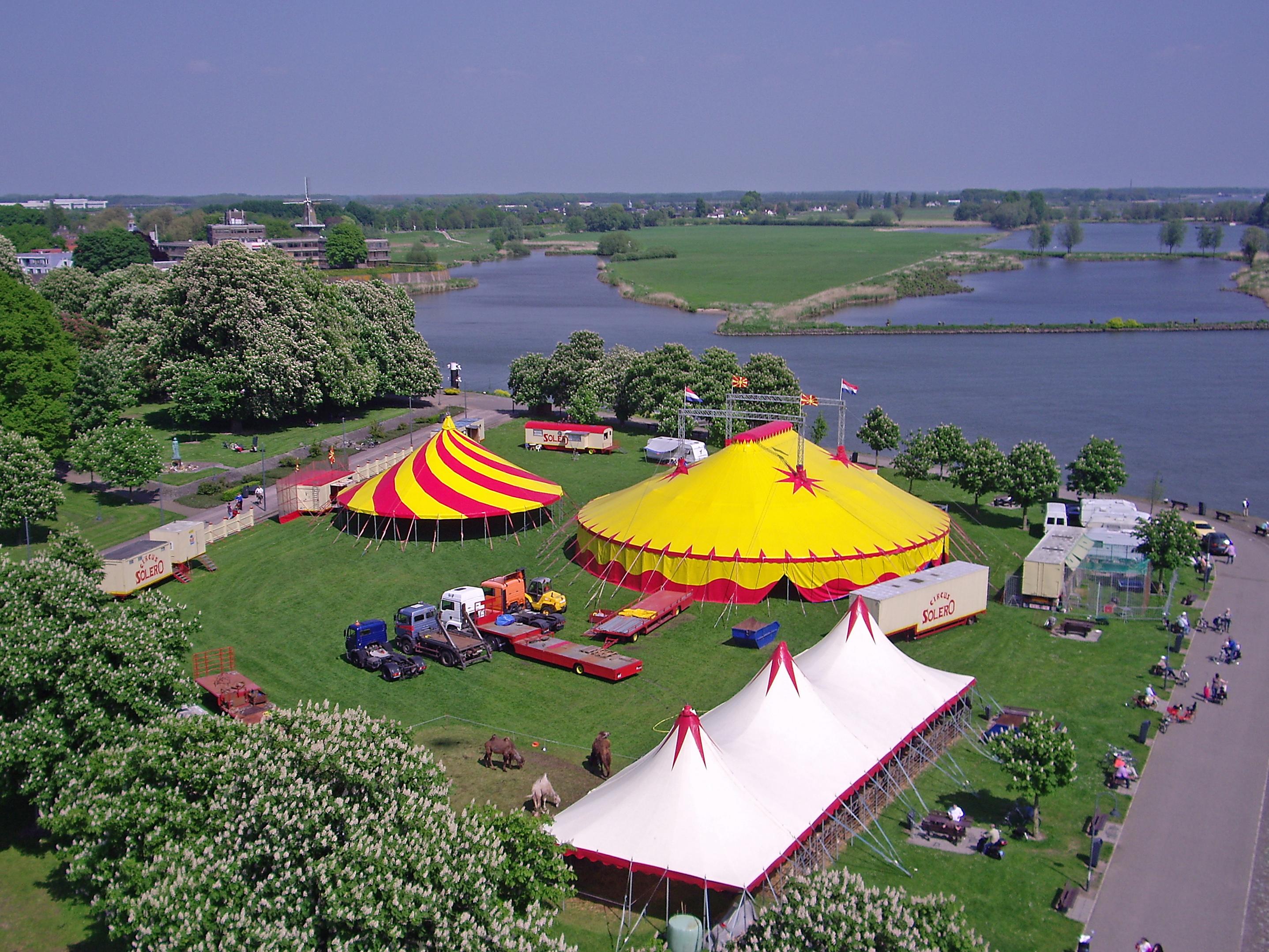 foto van bovenaf van circus Solero op een stuk gras bij het water