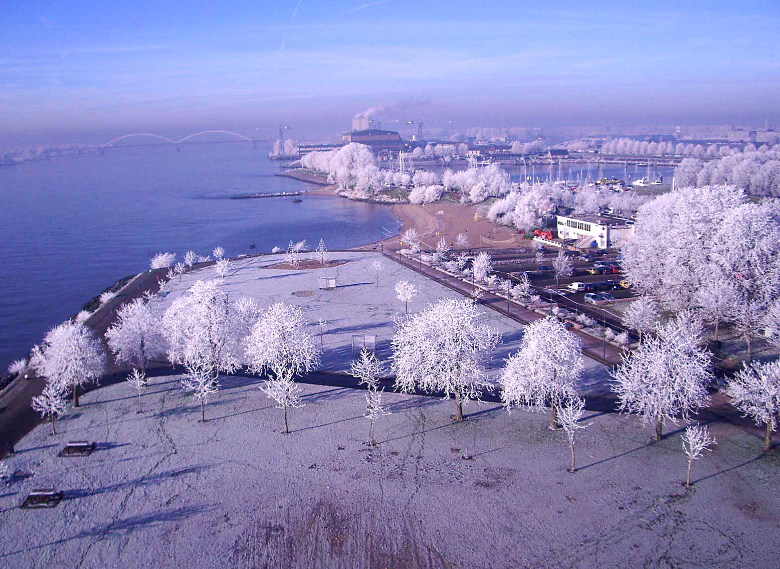 foto van bovenaf van sneeuwlandschap bij water met bruggen in de verte