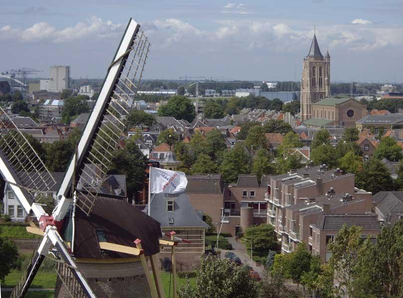 foto van  bovenaf van een stad met molen, huizen en een kerk