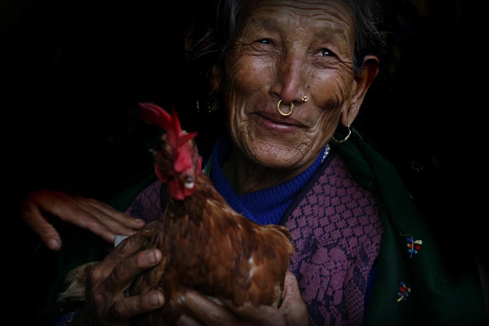 foto van een vrouw met een ring door haar neus en een kip in haar handen