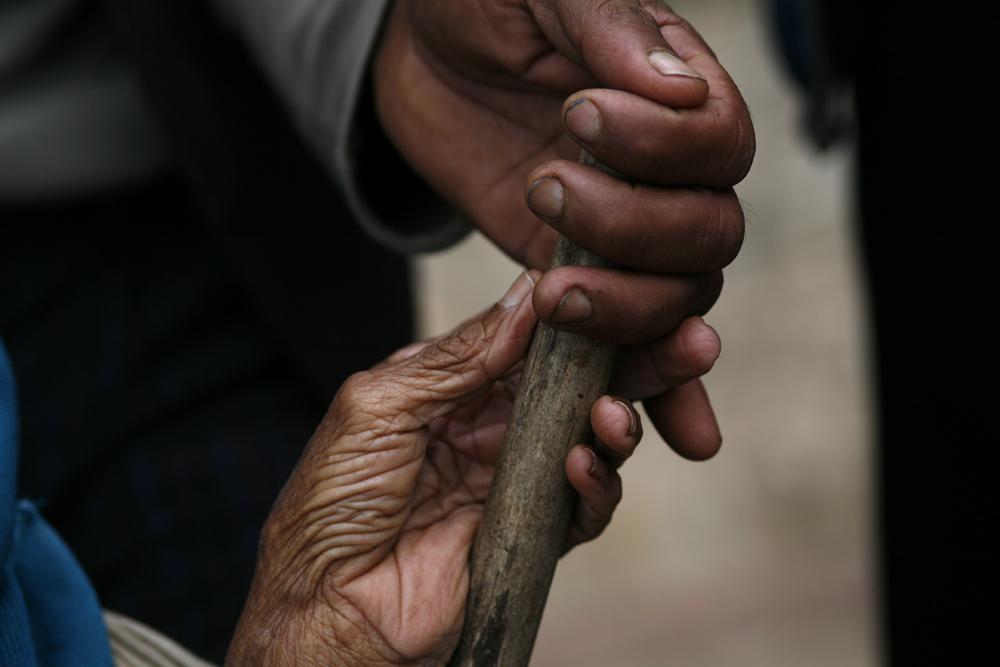 foto van twee handen van een oud en jong mens die een stok vasthouden