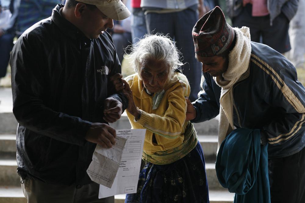 foto van een oude blinde vrouw die ondersteund wordt door twee mannen