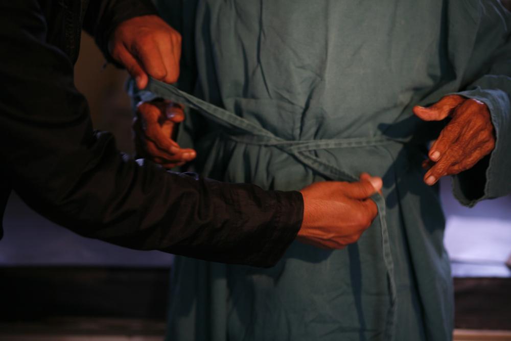 foto van het vastmaken van een band om een schort heen met vier handen