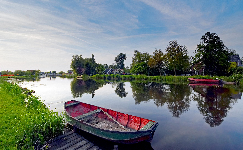 foto van bootjes in een rivier in een polderlandschap