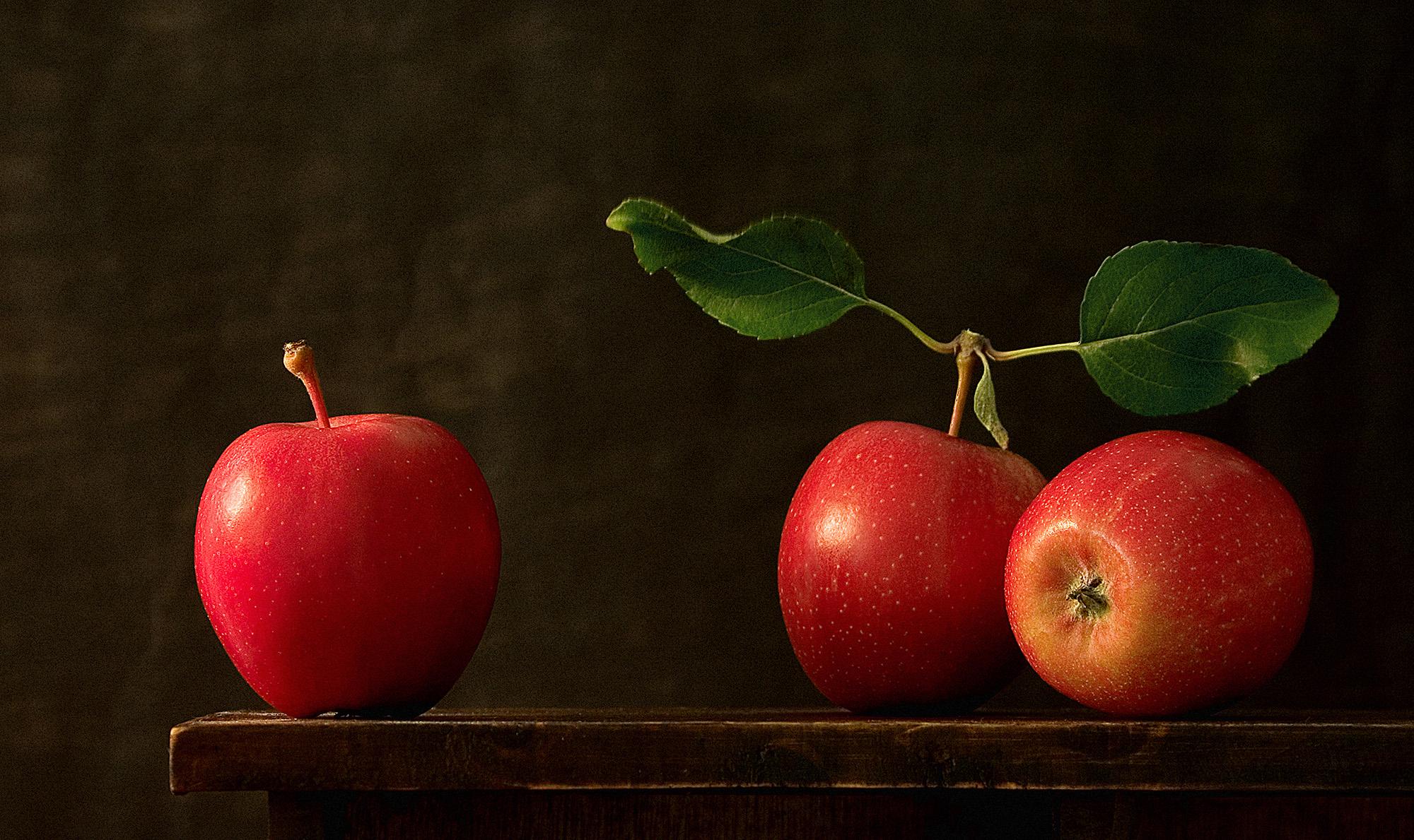 foto van drie rode appels op een tafel