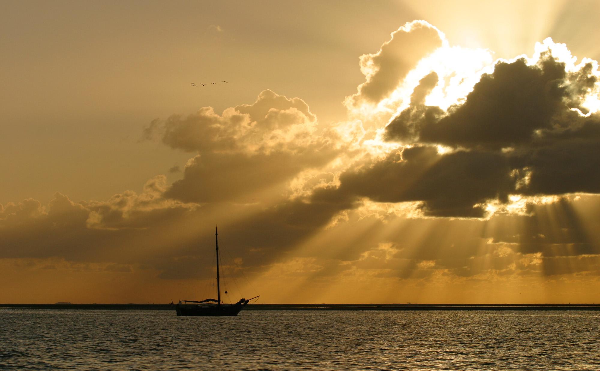 foto van een zeilboot op water met wolkenlucht waar zon doorheen schijnt