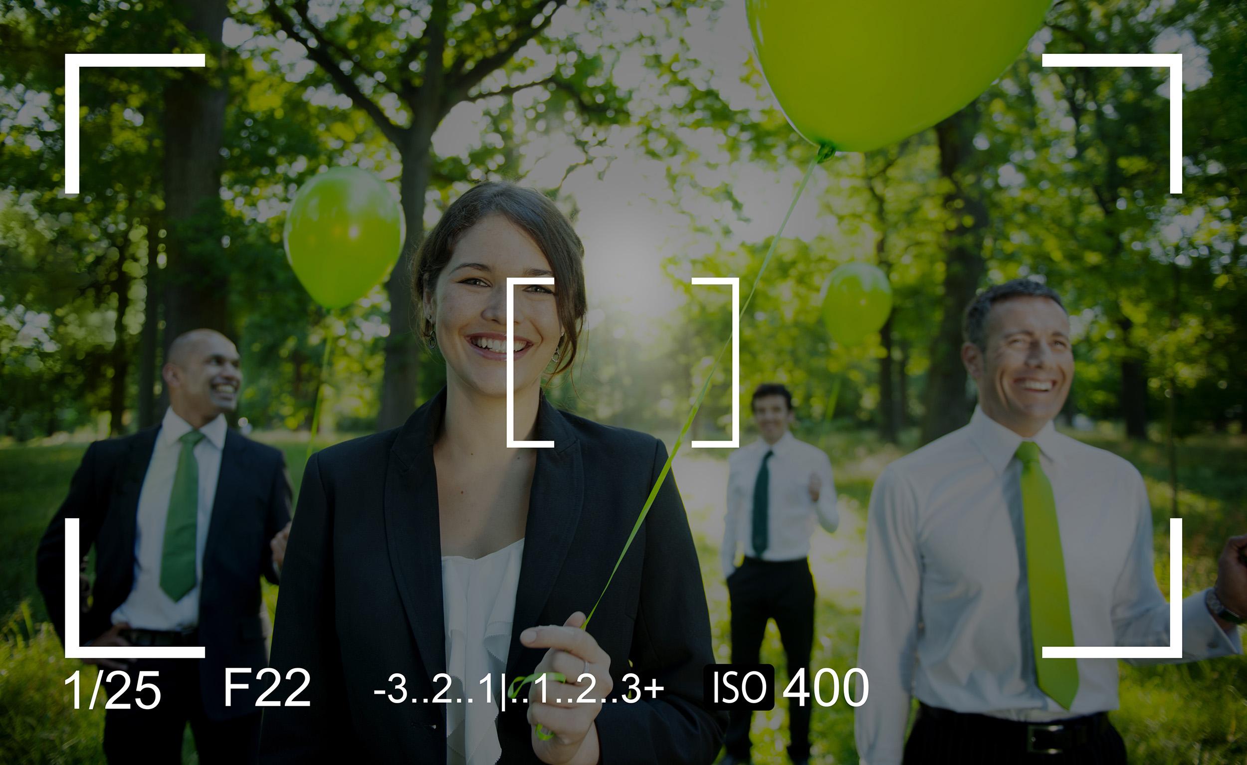 foto van een meisje en drie mannen in een bos met een groene ballon in hun hand met cameradetails eroverheen zoals 1/25f