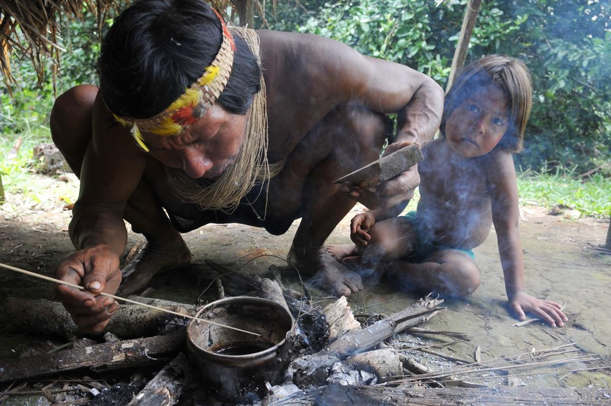 foto van een indiaan die hurkend iets kookt op vuurtje in een potje met kind ernaast