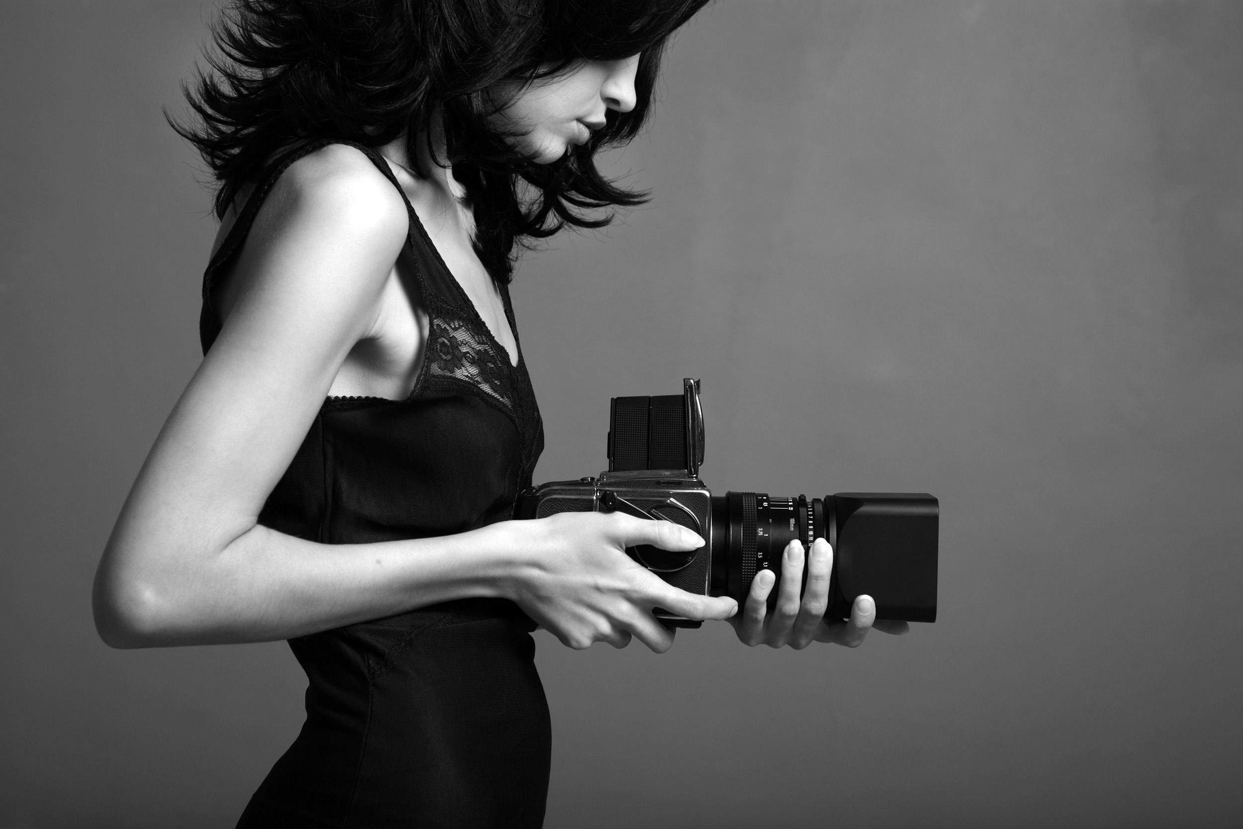 foto van de zijkant van een vrouw in zwartwit die een camera vasthoudt