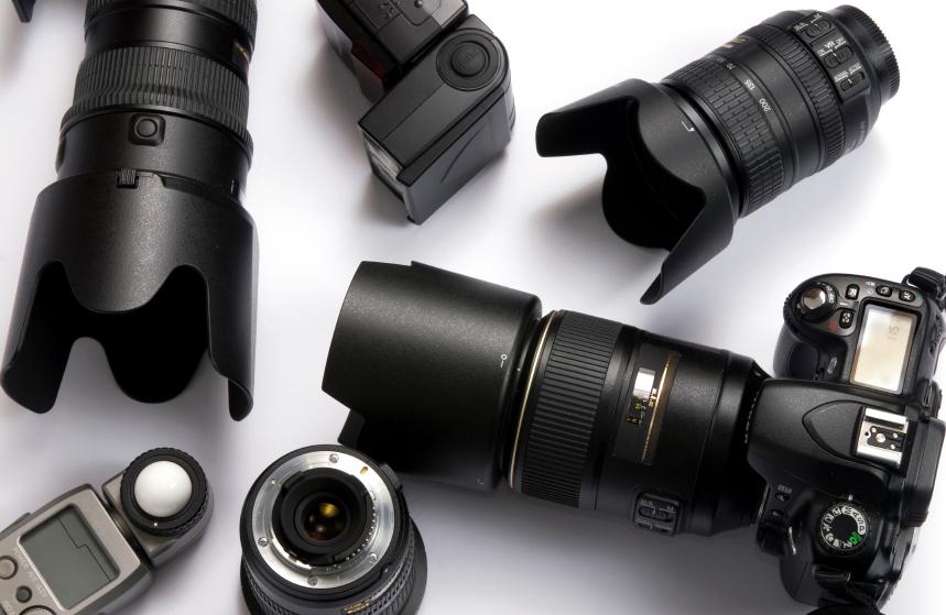 foto van allerlei camera's en objectieven op een tafel in zwartwit