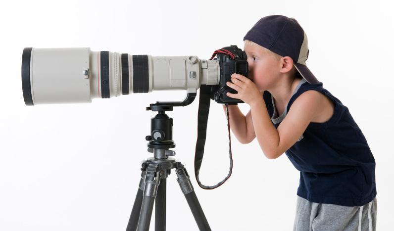 foto van een jongetje met een petje op die door een megagrote camera kijkt op een statief