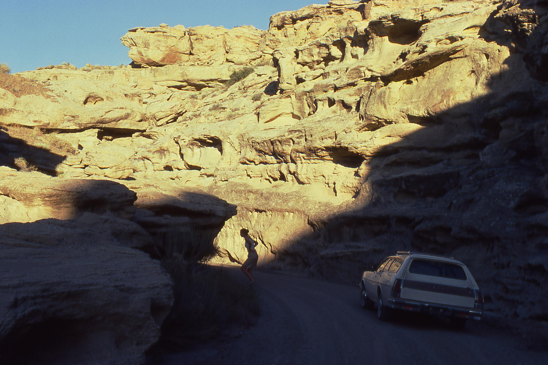 foto van een gebergte in Californië met zon erop en onder in de schaduw een auto op een weg en een vrouw die naar de overkant loopt