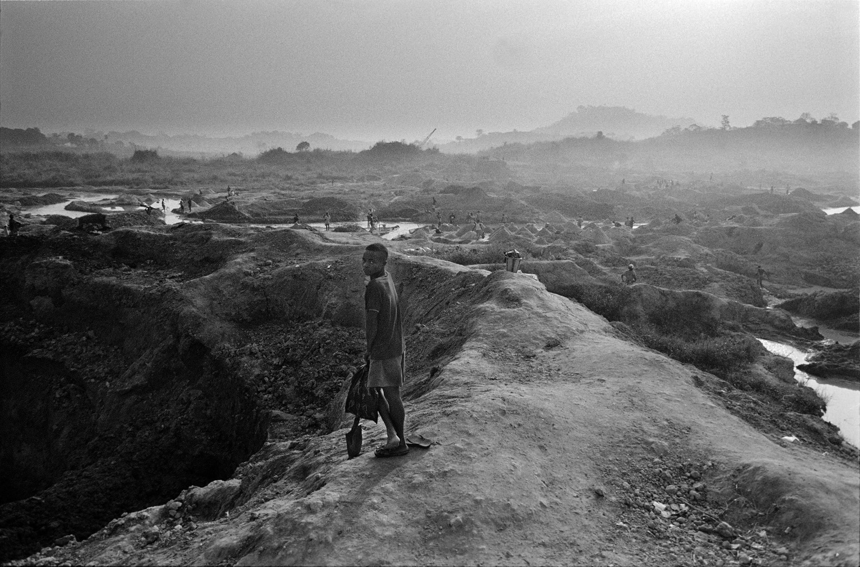 zwartwit foto van een jongen met een schep in een landschap in Rwanda waar hij naar diamanten moet graven
