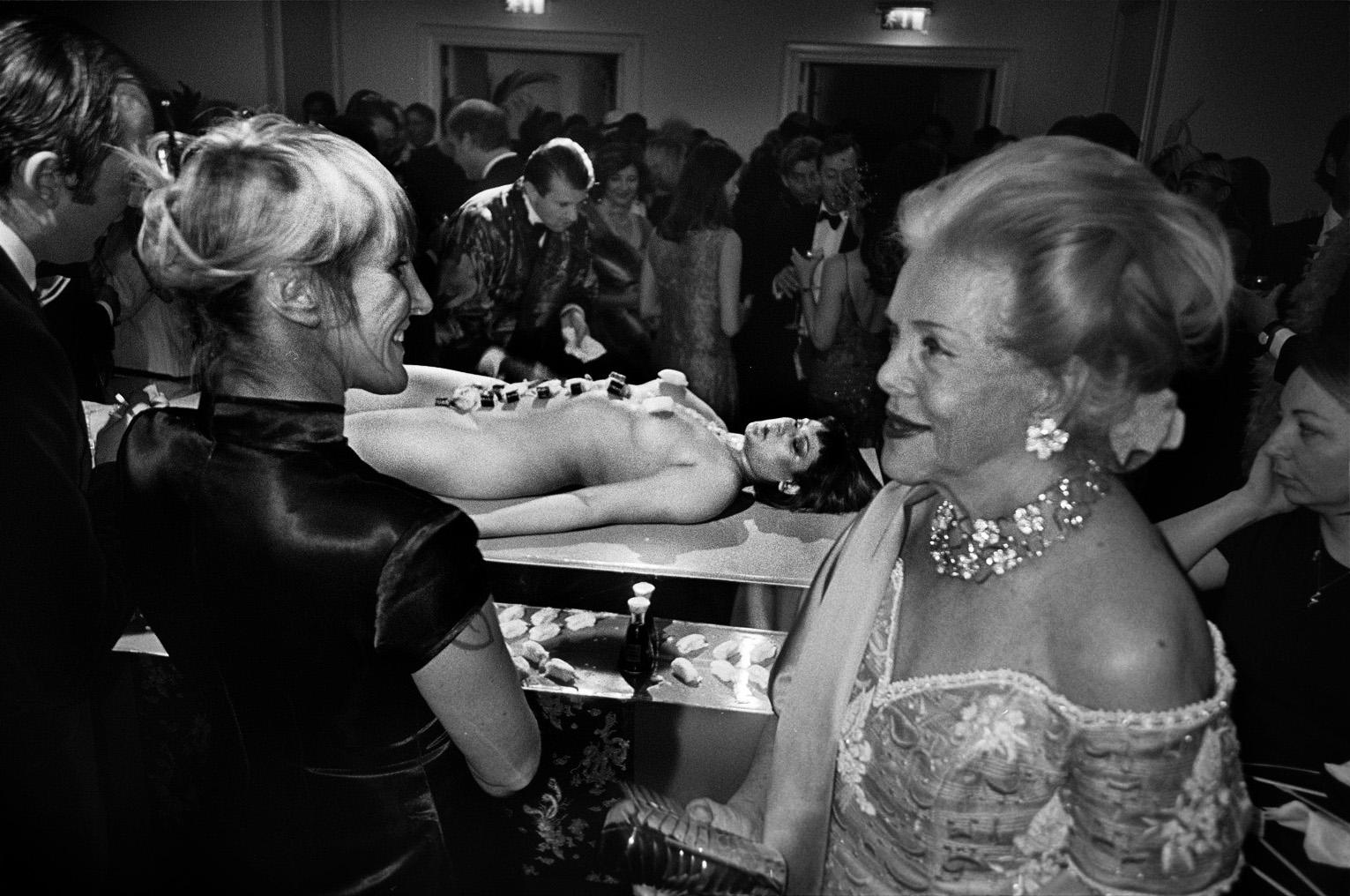 foto van rijke mensen met diamanten om op een feest waar in het midden een naakte vrouw ligt met stenen? op haar buik